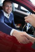Customer receiving car keys while shaking hand — Stock Photo