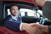 Woman giving car keys while shaking hand — Stock Photo
