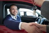 Woman giving car keys while shaking hand — Stock Photo