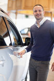 Man holding a car handle while smiling — Stock Photo