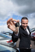 Happy dealer holding car keys by his fingertips — Stock Photo