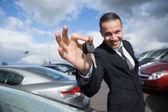 Happy dealer holding car keys — Stock Photo