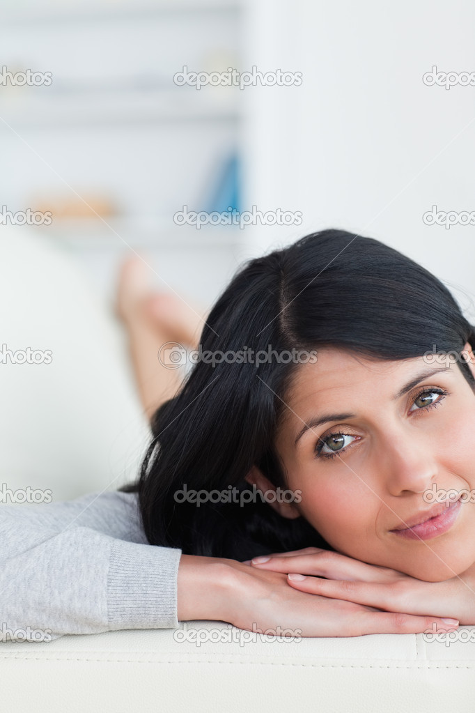Close-up of a woman resting her head on a sofa in a living room  Stock Photo #14070402