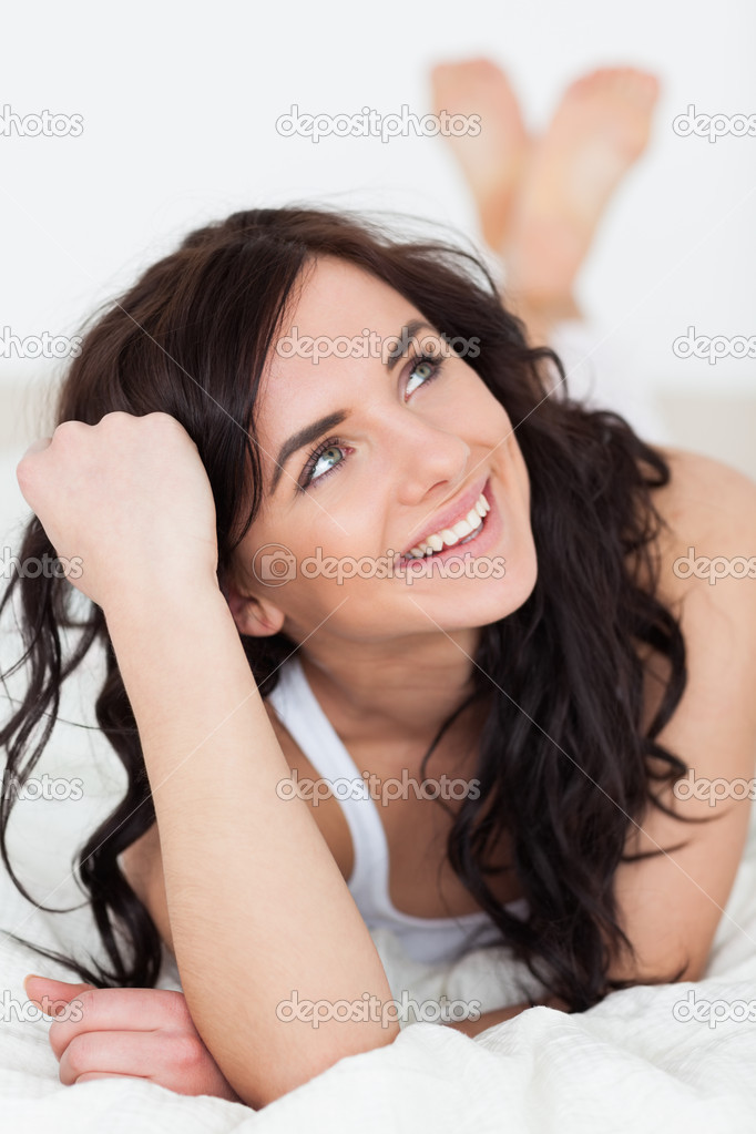 Smiling woman thinking while lying on her bed in her bedroom — Stock Photo #14070695
