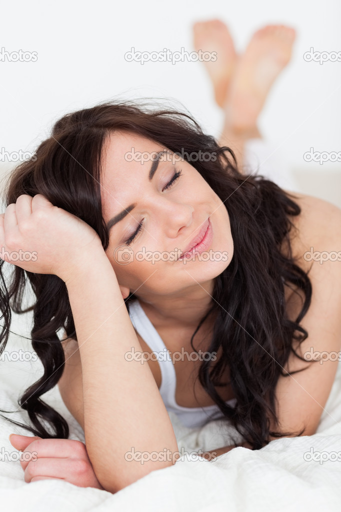 Peaceful woman closing her eyes while lying on her bed in her bright room — Stock Photo #14070700