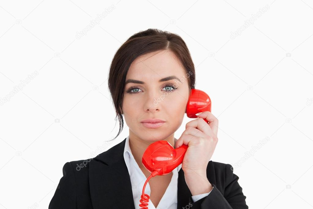 Attractive woman in suit using a red dial telephone against white background — Stock Photo #14072147