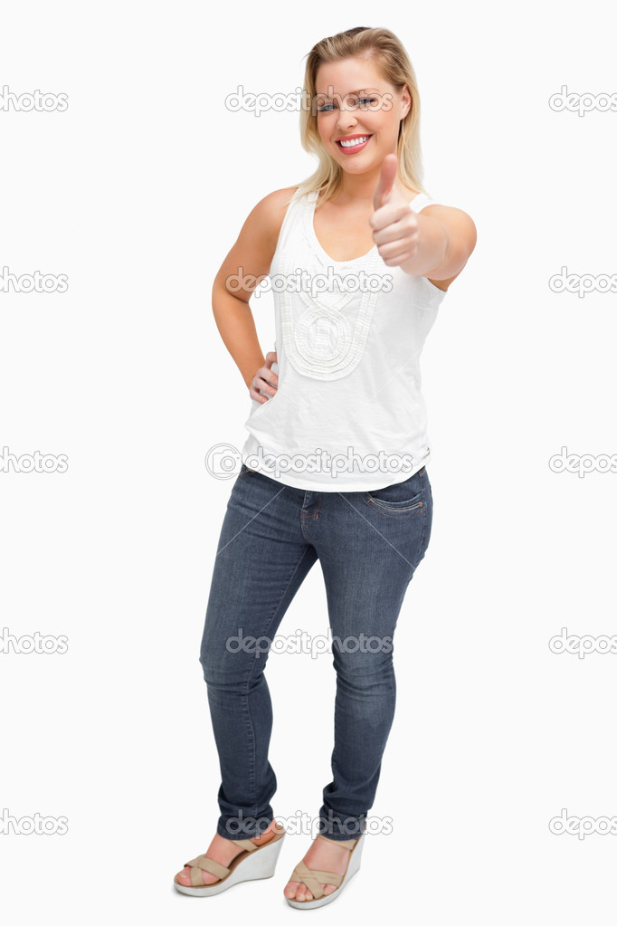 Cheerful blonde woman showing her thumbs up against a white background — Stock Photo #14072626