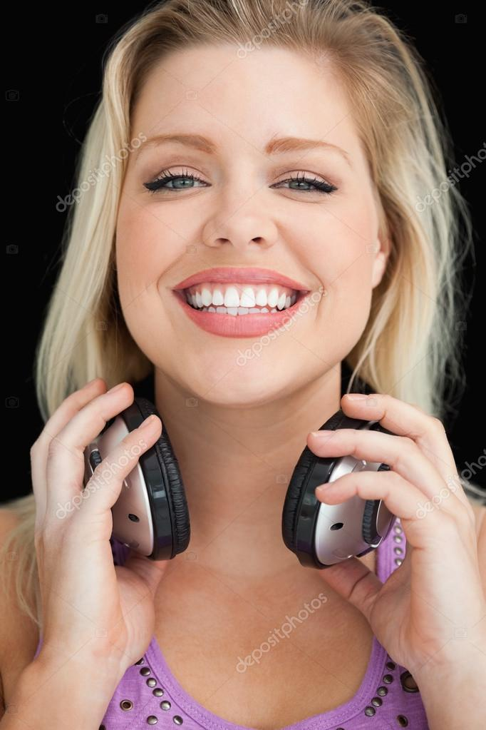 Happy blonde woman proudly holding her headphones against a black background  Stock Photo #14072980