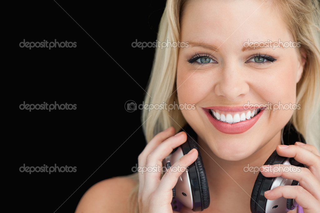 Smiling woman standing while holding her headphones against a black background — Stock Photo #14072981