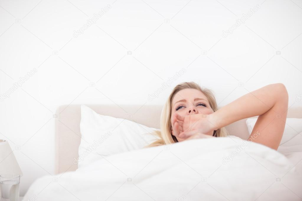 Young blonde yawning in her bed  Stock Photo #14075757