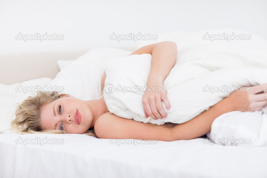 Young woman lying under a white duvet on her bed — Stock Photo #14075780