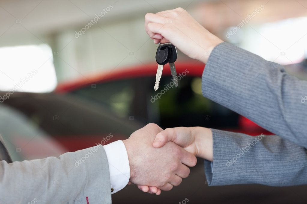 Close up of a woman shaking hand to a man in a dealership — Stock Photo #14078258