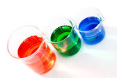 Three beakers of different colour and size — Stock Photo