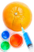 Beakers next to an orange piercing by a syringe — Stock Photo