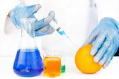 Chemist injecting product in an orange — Stock Photo