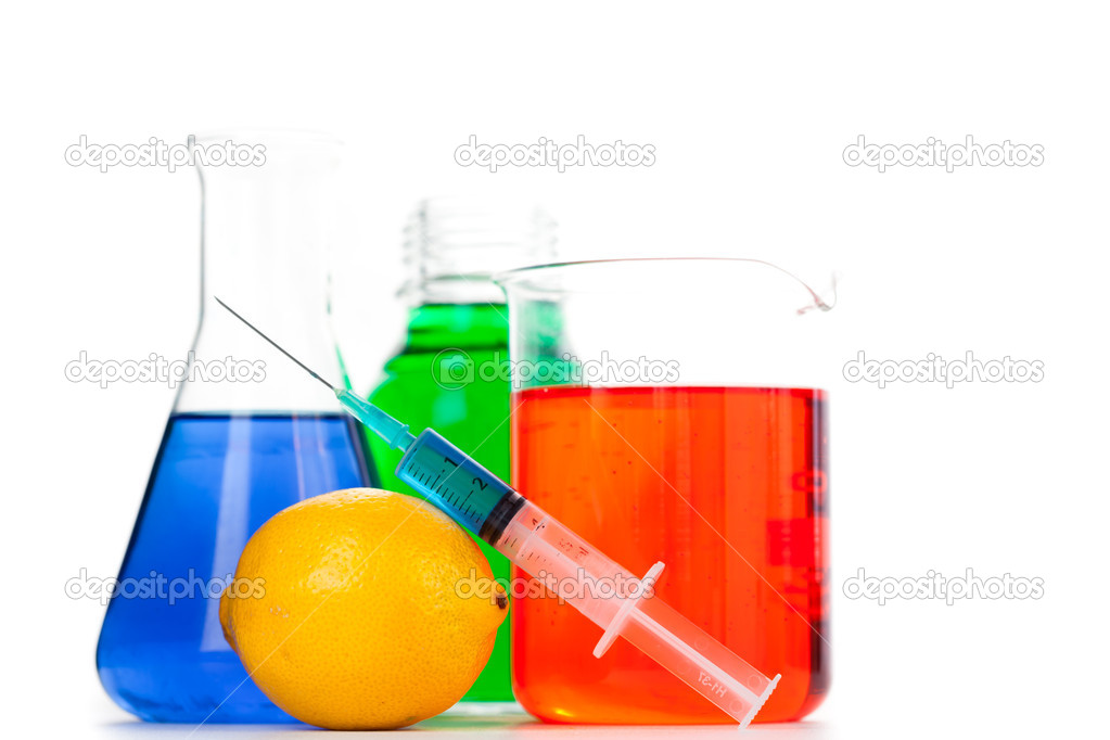 Syringe putting on an orange next to beakers against a white background — Stock Photo #14081746