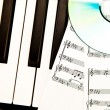 Compact disc and music scores placed on piano  — Stok fotoğraf