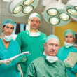Surgeon sitting while crossing his hands with a team behind him — Stock Photo