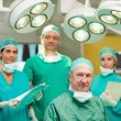 Smiling surgeon sitting with a team behind him — Stock Photo #14146902
