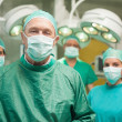 Smiling surgeon posing with a team — Stock Photo #14146908