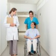 Nurse pushing a patient in a wheelchair while talking to a docto — Stock Photo