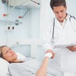 Doctor looking at his chart while holding hand of his patient — Stock Photo