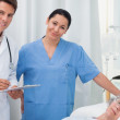 Doctor and nurse looking at camera next to a patient lying — Stock Photo #14148303