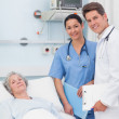 Patient with her doctor and nurse looking at camera — Stock Photo