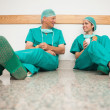 Surgeons talking while sitting in the floor — Stock Photo