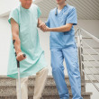 Foto de Stock  : Male nurse assisting patient