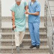 Stock Photo: Male nurse assisting patient on stairs