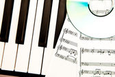 Compact disc and music scores placed on piano — Stock Photo