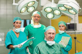 Smiling surgeon sitting with a team behind him — Stock Photo