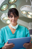 Woman surgeon holding a tactile tablet — Stock Photo