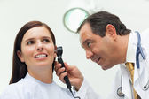 Lekarz za pomocą otoskop patrzeć na ucho jego pacjent — Zdjęcie stockowe