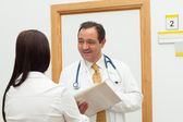 Smiling doctor holding a file while talking to a woman — Stock Photo