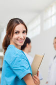 Nurse smiling while holding files and standing with a doctor and — Stock Photo