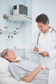 Doctor standing while holding a chart — Stock Photo