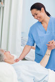 Nurse smiling to a patient while holding her hand — Stock Photo