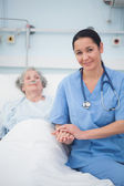 Nurse sitting on the bed next to a patient — Stock Photo