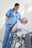 Elderly patient in a wheelchair next to a nurse — Stock Photo