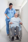 Elderly patient in a wheelchair looking at a nurse — Stock Photo
