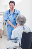 Nurse smiling while holding the hands of a patient — Stock Photo