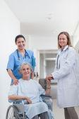 Doctor junto a un paciente en silla de ruedas — Foto de Stock