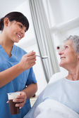 Nurse feeding a patient — Stock Photo