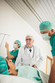 Doctor and surgeon looking at a female patient — Stock Photo
