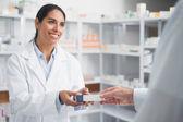 Farmacista sorridente dando una scatola con un medico — Foto Stock
