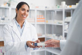 Smiling pharmacist giving a box to a doctor — Foto Stock