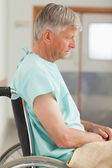 Sad man sitting in a wheelchair — Stock Photo