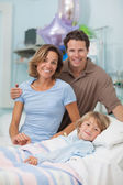 Child lying on a medical bed next to his parents — Stock Photo